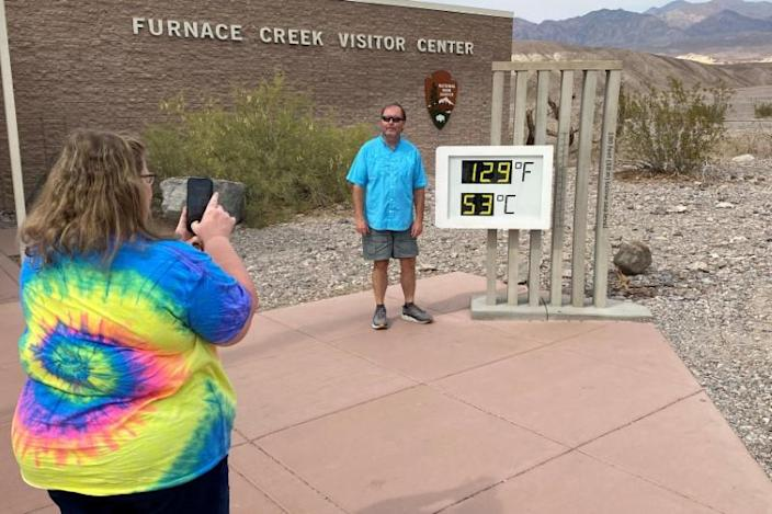 Tourists pose by thermometer in Death Valley