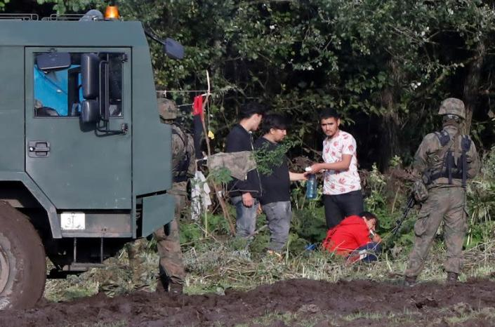FILE PHOTO: Polish border guard officers stand guard next to a group of migrants stranded on the border between Belarus and Poland near the village of Usnarz Gorny