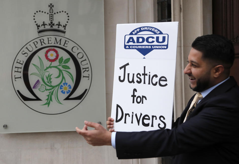 Uber driver and president of the (ADCU), App Drivers & Couriers Union, Yaseen Islam poses with a poster outside the Supreme Court in London, on 19 February. Photo: Frank Augstein/AP
