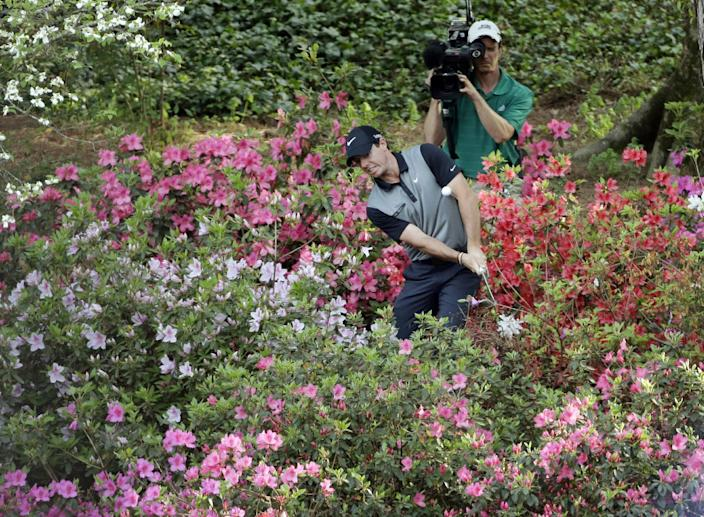 Rory McIlroy, of Northern Ireland, hits out of the azaleas to the 13th green during the second round of the Masters golf tournament Friday, April 11, 2014, in Augusta, Ga. (AP Photo/David J. Phillip)