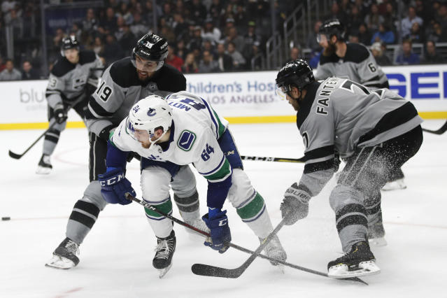 Vancouver Canucks' Tyler Motte, center, is pressured by Los Angeles Kings' Oscar Fantenberg, right, of Sweden, and Alex Iafallo during the first period of an NHL hockey game Saturday, Nov. 24, 2018, in Los Angeles. (AP Photo/Jae C. Hong)