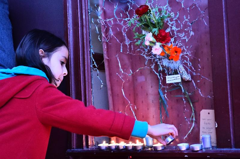 "A girl lights a candle November 15, 2015 in front of a broken window at ""Le carillon"" restaurant, site of one of the November 13 jihadist attacks that has galvanized Paris and the world (AFP Photo/Loic Venance)"