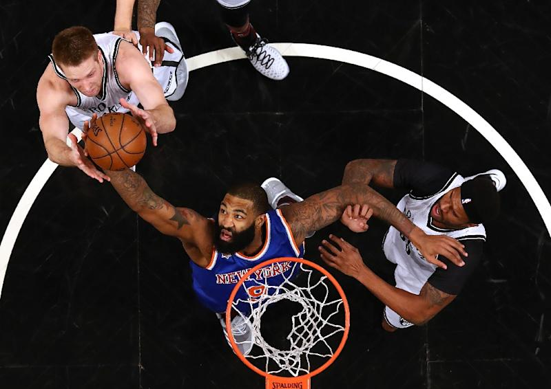 Kyle O'Quinn of the New York Knicks rebounds against Trevor Booker and Justin Hamilton of the Brooklyn Nets during their game February 1, 2017
