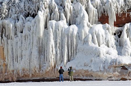 Sightseers look at a frozen rock face along the Apostle Islands National Lakeshore of Lake Superior, the world's largest freshwater lake, near Cornucopia, Wisconsin February 14, 2014. REUTERS/Eric Miller