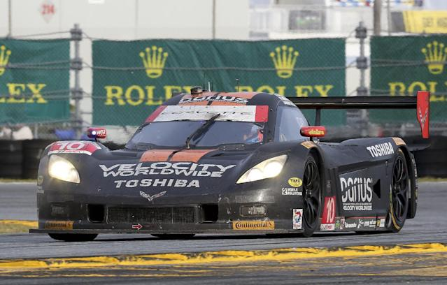 Ricky Taylor drives the Wayne Taylor Racing Corvette DP through the east horseshoe turn during the IMSA Series Rolex 24 hour auto race at Daytona International Speedway in Daytona Beach, Fla., Sunday, Jan. 26, 2014.(AP Photo/David Graham)