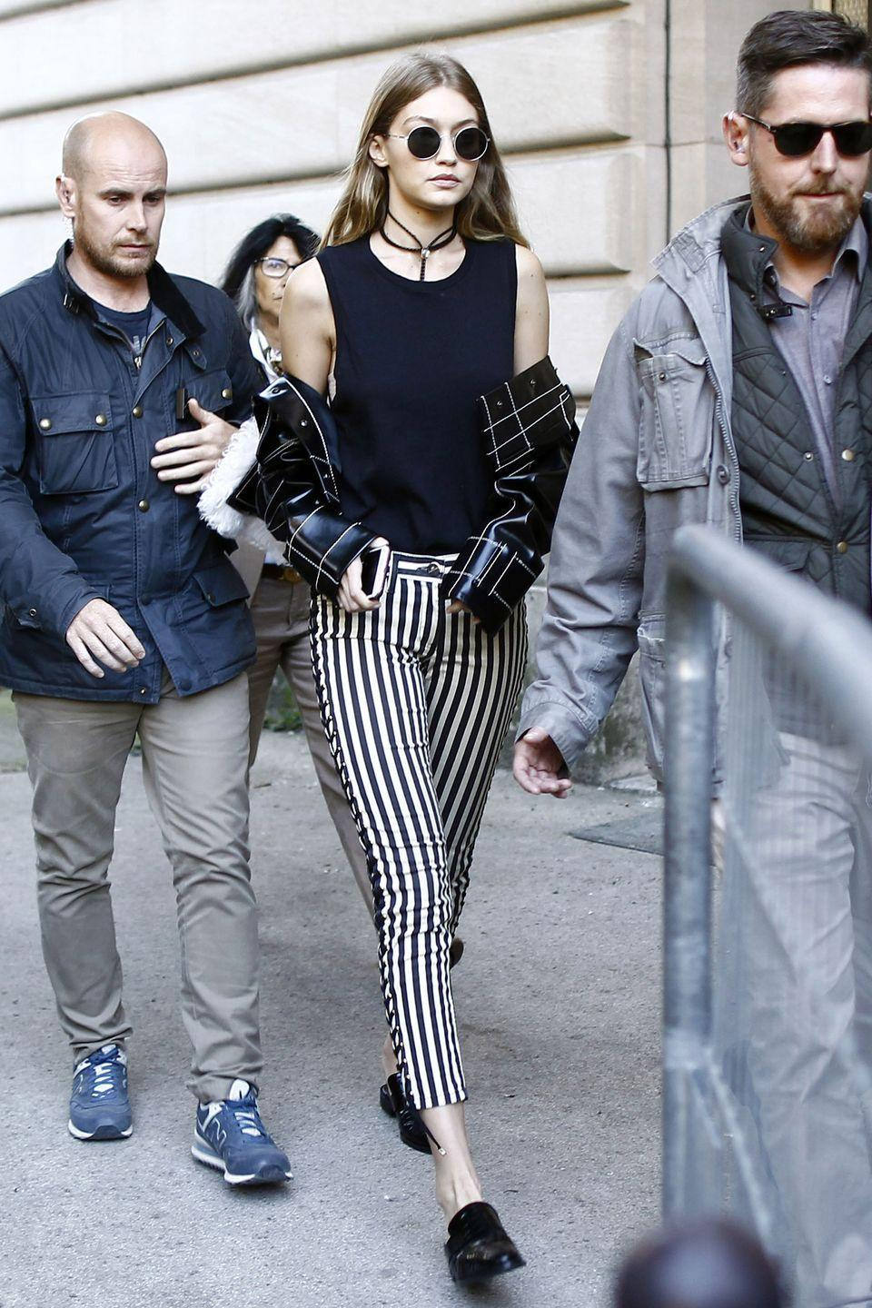 <p>Wearing a black tank top, lace-up striped pants, mule loafers, an embroidered leather jacket, rounded sunglasses and a choker while leaving the Giambattista Valli show in Paris.</p>