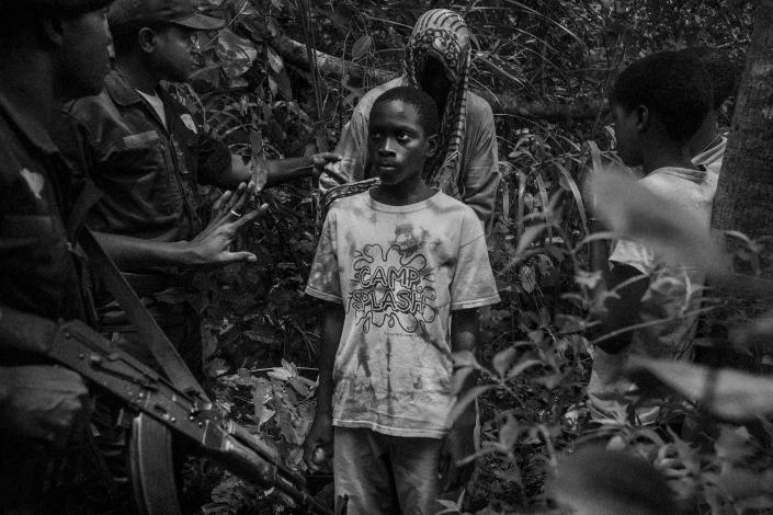 <p>Guinean military police approach a group of children walking through a forest area near Bissau border, Guinea-Bissau, June 15, 2015. Earlier in March 2015, Guinea-Bissau authorities found 54 children hidden inside five vehicles that were crossing the border to Senegal, but Senegalese authorities continue to fail to prosecute traffickers. (Photograph by Mario Cruz) </p>
