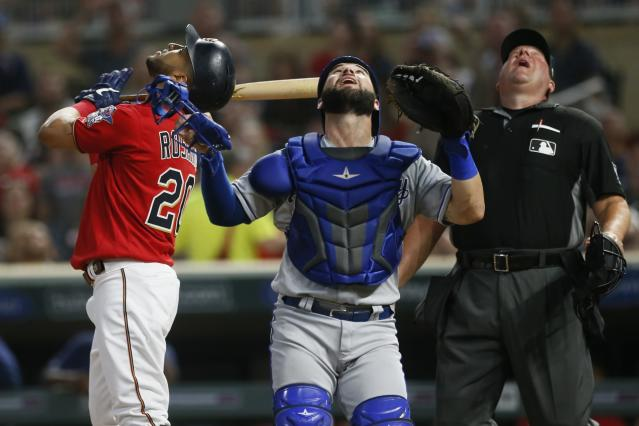 Minnesota Twins' Eddie Rosario, left, Kansas City Royals catcher Nick Dini, center and plate umpire Sam Holbrook watch Rosario's popup before Dini made the catch in the first inning of a baseball game Friday, Sept. 20, 2019, in Minneapolis. (AP Photo/Jim Mone)