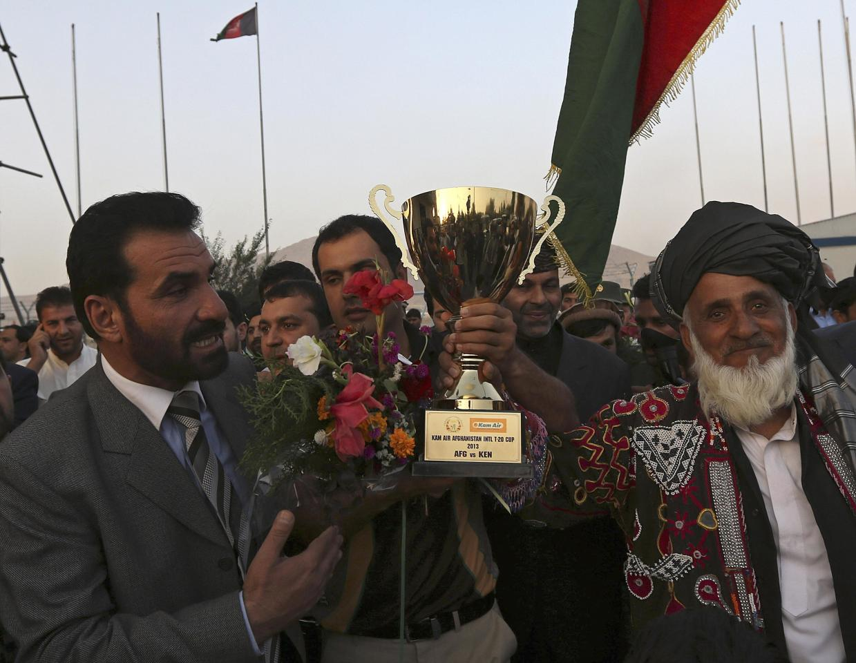 Afghan cricket team captain Mohammad Nabi Esa Khil (C) holds the ACC Cup after the team's arrival in Kabul, in this October 12, 2013 file photo, following Afghanistan's qualification for the 2015 Cricket World Cup. Surrounded by thousands of makeshift tents in the dusty refugee camp he called home, not even in his wildest dreams could Mohammad Nabi have believed that his decision to while away the hours with a miniature cricket bat would lead him to play in the 2015 World Cup. To match feature CRICKET-AFGHANISTAN/ 