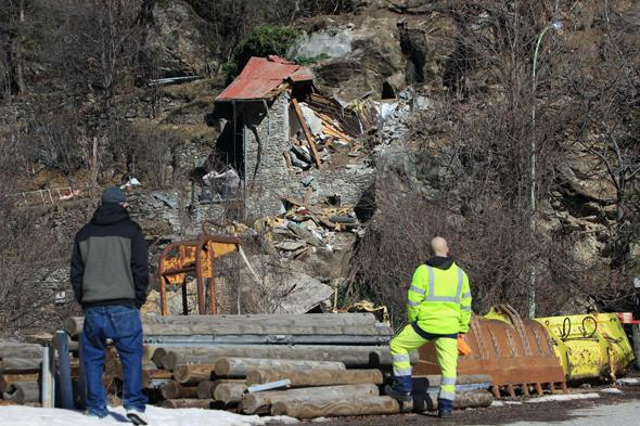 Two people look at the mountain cottage destroyed by a rockslide which killed two children aged seven and ten, on February 23, 2014 in Isola Village (French Alps). Both children and their families from the region, arrived yesterday in the village where they occupied an old barn located on a cliff. AFP PHOTO / JEAN CHRISTOPHE MAGNENET        (Photo credit should read JEAN CHRISTOPHE MAGNENET/AFP/Getty Images)
