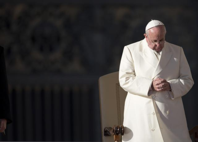 Pope Francis prays during his weekly general audience in St. Peter's Square at the Vatican, Wednesday, Dec. 18, 2013. (AP Photo/Alessandra Tarantino)