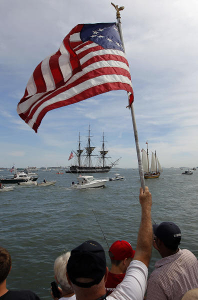 An onlooker waves a colonial era flag as the USS Constitution passes through Boston Harbor in Boston, Sunday, Aug. 19, 2012. The USS Constitution, the U.S. Navy's oldest commissioned war ship, sailed under her own power during the event Sunday for the first time since 1997. The sail was held to commemorate the 200th anniversary of the ship's victory over HMS Guerriere in the War of 1812. (AP Photo/Steven Senne)