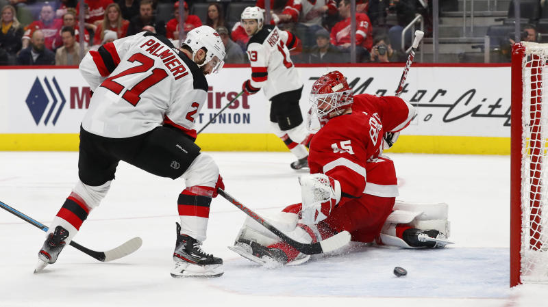 New Jersey Devils right wing Kyle Palmieri (21) scores a goal on Detroit Red Wings goaltender Jonathan Bernier (45) in the second period of an NHL hockey game Tuesday, Feb. 25, 2020, in Detroit. (AP Photo/Paul Sancya)
