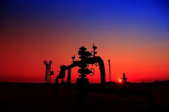 The silhouette of a natural gas well at sunset.