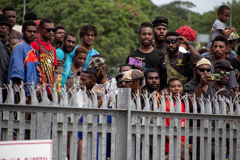 This picture taken on March 14, 2021 shows a crowd of people - none wearing face masks, nor social distancing - gathered outside the airport in Port Moresby to bid farewell to the casket of PNG's first prime minister Michael Somare, who died late February. Source: Getty