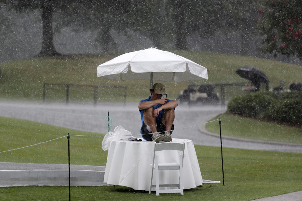 Security worker Raymond Fracchia takes shelter under an umbrella as rain falls during a practice round at the World Golf Championship-FedEx St. Jude Invitational Wednesday, July 29, 2020, in Memphis, Tenn. (AP Photo/Mark Humphrey)