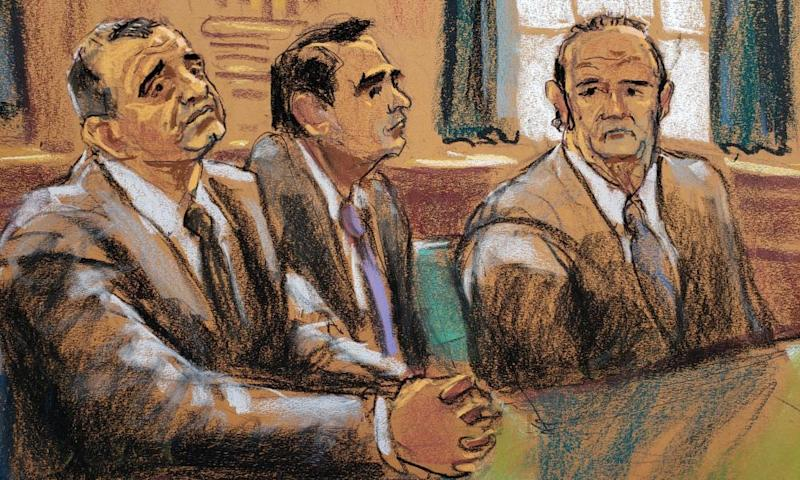 Lev Parnas, left, and Igor Fruman sit either side of lawyer Todd Blanche during their arraignment in New York City on 23 October 23.