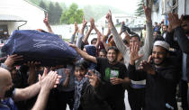 Migrants celebrate holding cricket gear after it arrived in Blazuj migrant camp in Bosnia's capital of Sarajevo Wednesday, May 19, 2021. The Rome-based Baobab Experience group brought cricket equipment for the migrants in the Blazuj camp and also the central town of Tuzla, offering a rare opportunity for relaxation and fun for the people who spend months, if not years, stuck in camps while fleeing war and poverty in their nations and chasing their dreams of a better future. (AP Photo/Kemal Softic)