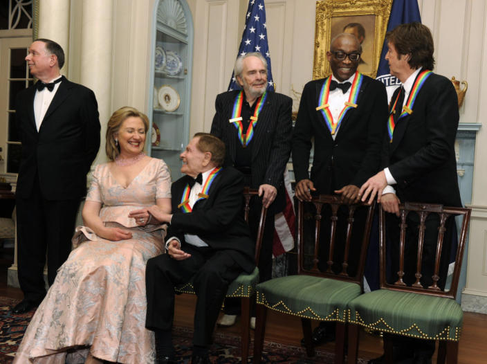 <p>Secretary of State Hillary Clinton chats with 2010 Kennedy Center honoree composer and lyricist Jerry Herman, as fellow honorees, left to right, singer and songwriter Merle Haggard, dancer, choreographer and director Bill T. Jones and songwriter, musician and former Beatle Sir Paul McCartney wait for a group photo after a gala dinner in Washington in December 2010. At left is Kennedy Center President Michael Kaiser. (Photo: Mike Theiler/Reuters)</p>