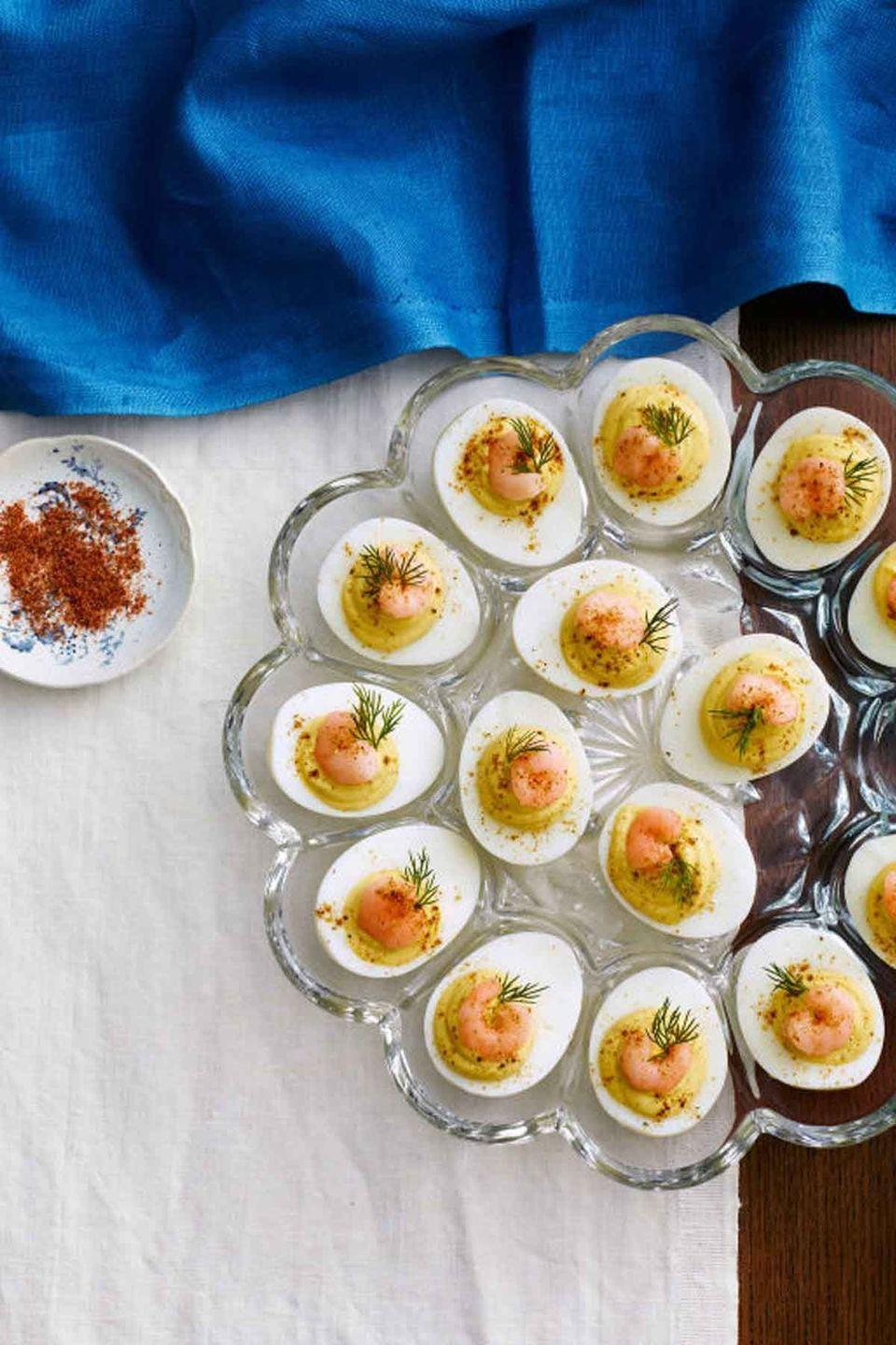 """<p>A taste of summer any time of year, these creamy deviled eggs incorporate Old Bay seasoning and pickled shrimp for an impressive dish. </p><p><a href=""""https://www.womansday.com/food-recipes/food-drinks/recipes/a39885/deviled-eggs-old-bay-shrimp-recipe-clx0414/"""" rel=""""nofollow noopener"""" target=""""_blank"""" data-ylk=""""slk:Get the Deviled Eggs with Old Bay Shrimp recipe."""" class=""""link rapid-noclick-resp""""><strong><em>Get the Deviled Eggs with Old Bay Shrimp recipe.</em></strong></a> </p>"""