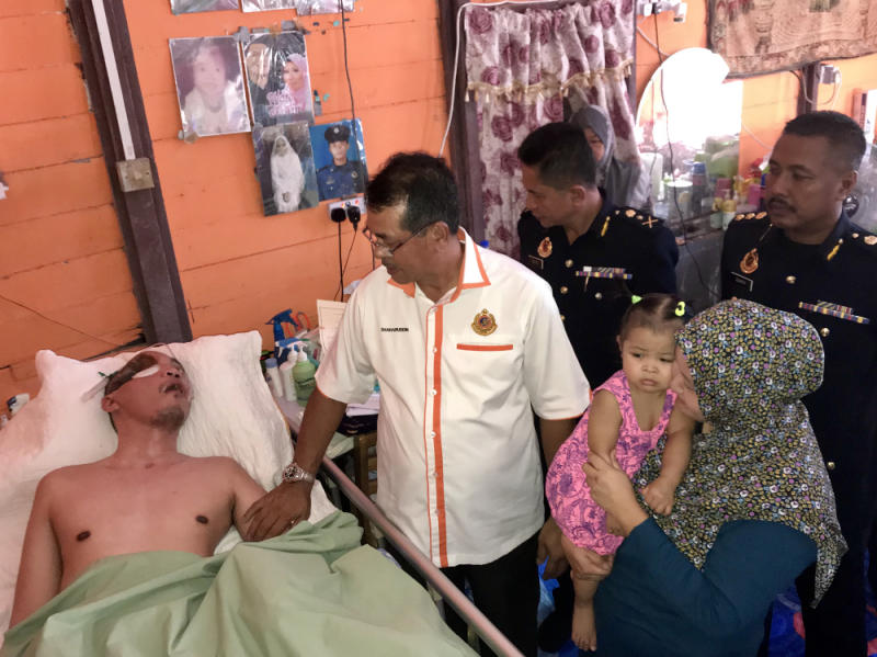 RTD director-general Datuk Seri Shaharuddin Khalid visits Mohd Syamaizar Mohamad Yahya (in bed) after presenting his retirement letter to him at the latter's family home in Pontian September 24, 2018. Also seen are Mohd Syamaizar's wife Rozita Faiman and daughter Dhia Nur Iriesya Airis. — Picture by Ben Tan