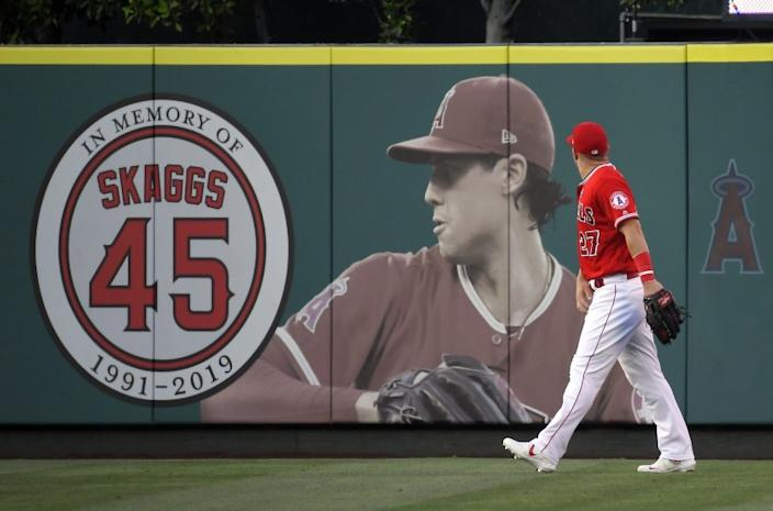 Los Angeles Angels center fielder Mike Trout walks by a picture of Tyler Skaggs in center field prior to a baseball game against the Baltimore Orioles, Thursday, July 25, 2019, in Anaheim, Calif. Skaggs died on July 1. (AP Photo/Mark J. Terrill)