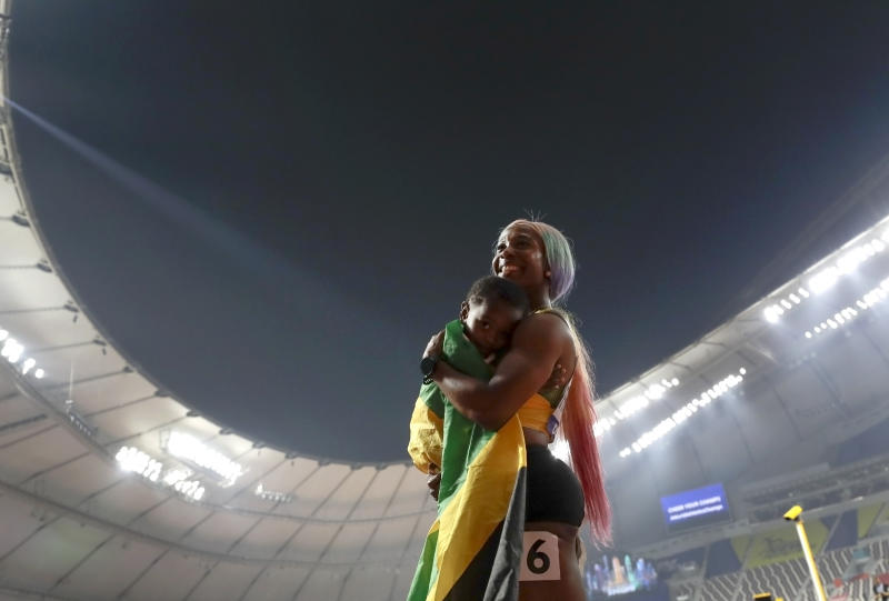 Shelly-Ann Fraser-Pryce, of Jamaica with son Zyon after winning the gold medal in the women's 100 meter final at the World Athletics Championships in Doha, Qatar, Sunday, Sept. 29, 2019. (AP Photo/Petr David Josek)