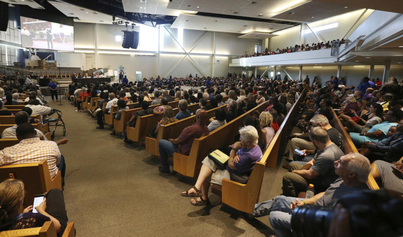 FILE - In this June 18, 2019 file photo people attend a community meeting in Phoenix. Still stinging from national outrage sparked this summer by a videotaped encounter of officers pointing guns and cursing at a black family, community members are holding low-key meetings aimed at helping Phoenix officials figure out how citizens could help oversee the city's officers. (AP Photo/Ross D. Franklin,File)