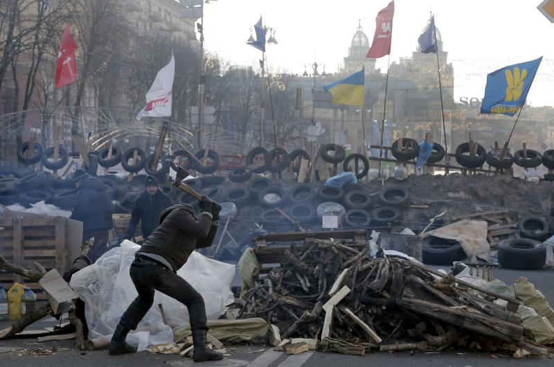 A pro-European Union activist chops wood at a barricade on the main street of Khreschatyk in Kiev, Ukraine, Monday, Dec. 23, 2013. Ukraine has been stricken with mass protests for over a month. Protesters are demanding Ukrainian President Viktor Yanukovych's resignation over his decision to ditch a pact with the European Union in favor of closer ties with Russia. (AP Photo/Efrem Lukatsky)