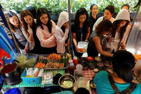 People queue to buy their lunch at a street food shop in Bangkok