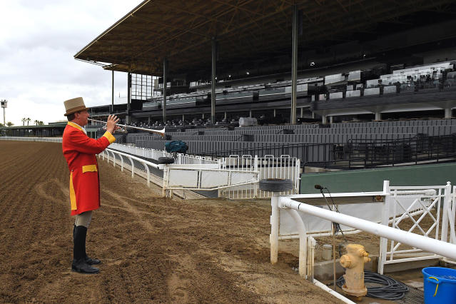 """Bugler Jay Cohen plays """"First Call"""" as he calls the riders to post for the first race at Santa Anita Park to empty stands Saturday, March 14, 2020, in Arcadia, Calif. (AP Photo/Mark J. Terrill)"""