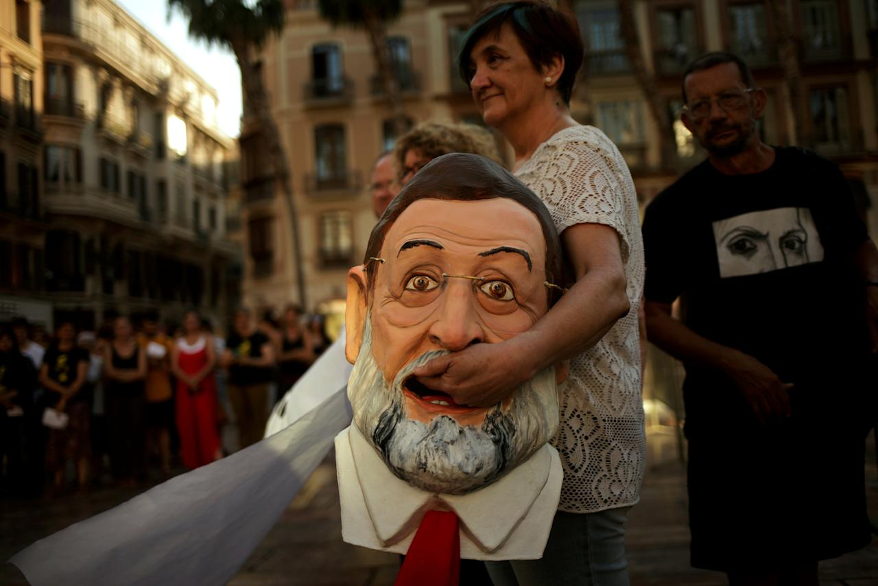 An activist of global anti-poverty charity Oxfam holds a mask depicting Spanish Prime Minister Mariano Rajoy as she takes part in a protest as part of a campaign to denounce the non-fulfillment of the Spanish government's commitments to welcome refugees, in downtown Malaga, southern Spain June 20, 2017. REUTERS/Jon Nazca