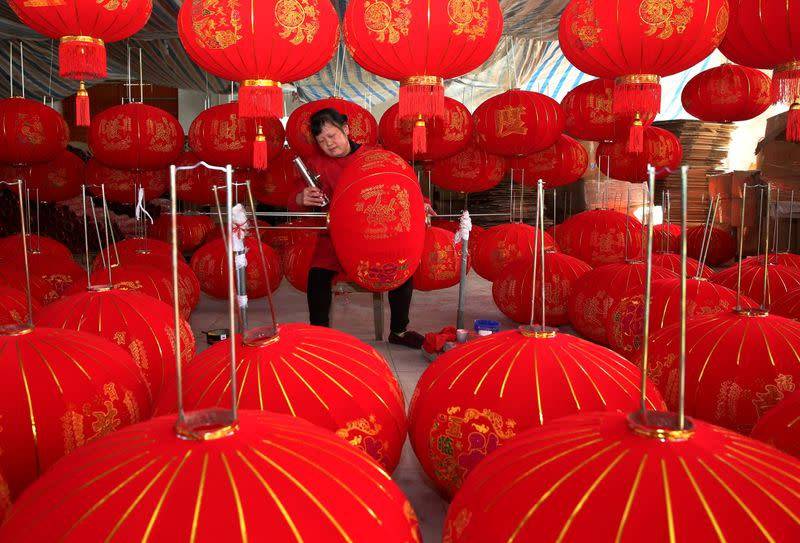 A villager makes red lanterns at a workshop in Anqing, Anhui