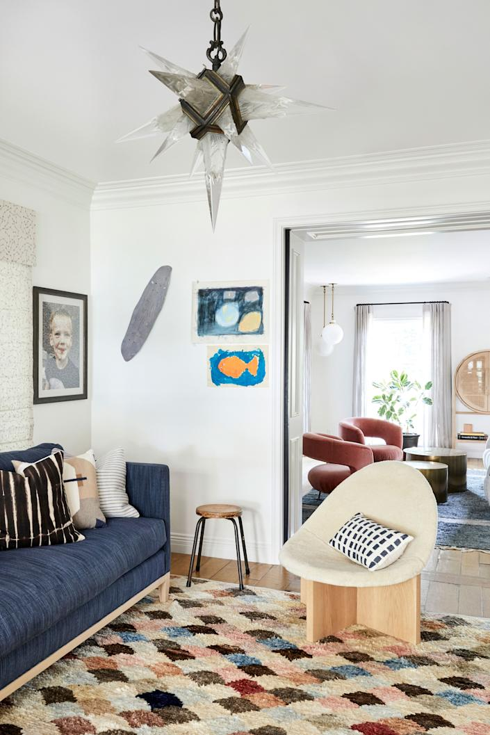 """<div class=""""caption""""> The room just off the living room is a dedicated kids' playroom, with lots of easy-to-clean textured fabrics. The hanging lantern predates Duff's children, however. """"I found that on <a href=""""https://www.1stdibs.com/"""" rel=""""nofollow noopener"""" target=""""_blank"""" data-ylk=""""slk:1stDibs"""" class=""""link rapid-noclick-resp"""">1stDibs</a>, like, 15 years ago,"""" she says. """"I had it hanging in my old house, in this room that we used to call the cognac room back in the day. Then it hung in a dining room, and then in a kitchen. It's one of those pieces that I am just obsessed with and that will follow me wherever I go. It's cool and it's really old."""" The scoop chair in shearling is by <a href=""""https://stahlandband.com/"""" rel=""""nofollow noopener"""" target=""""_blank"""" data-ylk=""""slk:Stahl + Band"""" class=""""link rapid-noclick-resp"""">Stahl + Band</a>. </div>"""