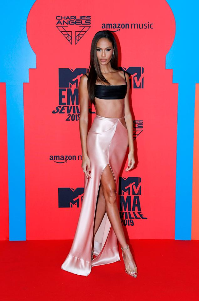 Joan Smalls wore a black crop top and pink satin skirt with a high slit to the MTV EMAs in Seville, Spain. The black and pink getup paired perfectly with her sleek straight hair and see-through stilettos.