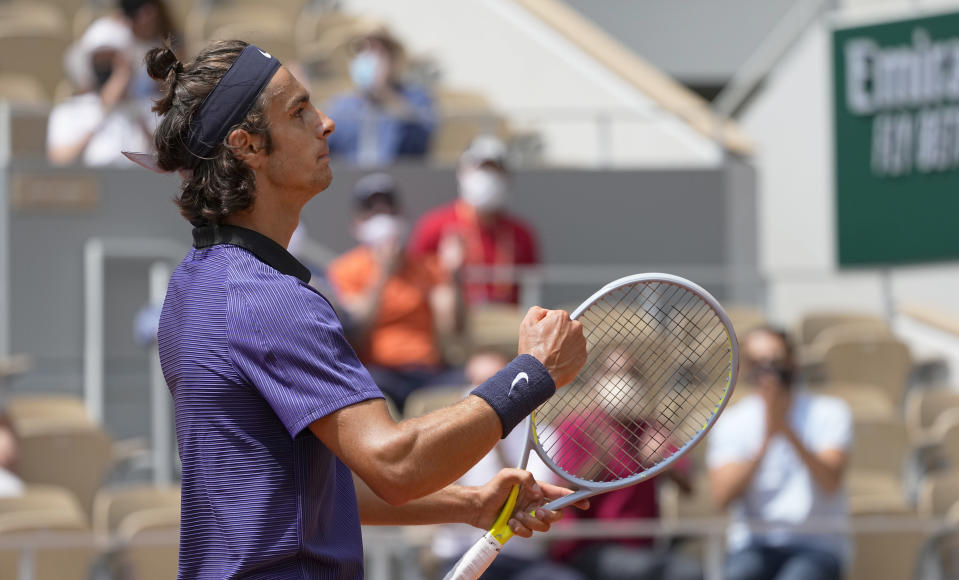 Italy's Lorenzo Musetti celebrates after winning the first set as he plays against Serbia's Novak Djokovic during their fourth round match on day 9, of the French Open tennis tournament at Roland Garros in Paris, France, Monday, June 7, 2021. (AP Photo/Michel Euler)
