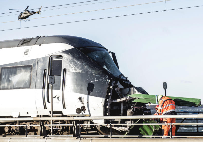 "Rescue workers at the site of a train accident on Great Belt Bridge in Nyborg, in Denmark, Wednesday, Jan. 2, 2019. At least six people were killed and 16 others injured early Wednesday when a Danish passenger train apparently hit falling cargo from a passing freight train as it crossed a bridge linking central Denmark's islands. Police spokesman Lars Braemhoej said that while ""we do not know precisely what caused the accident,"" one possible cause was that cargo from a passing freight train fell off and hit the passenger train. He added there was ""considerable damage"" on the passenger train. (Tim Kildeborg Jensen/Ritzau Scanpix via AP)"
