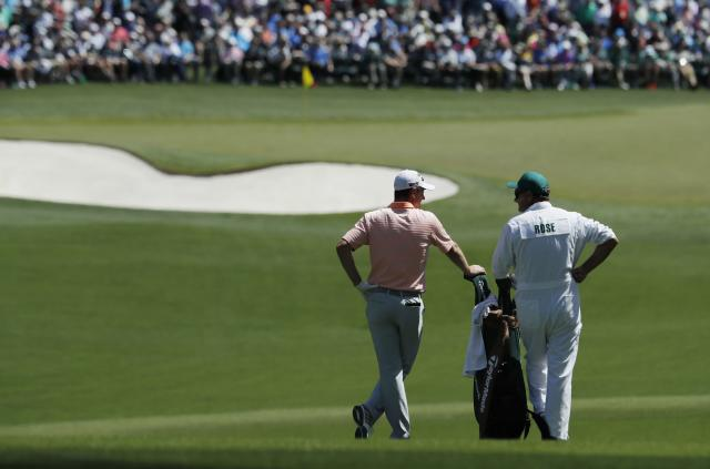 Justin Rose of England chats with his caddie Mark Fulcher on the second fairway before hitting his second shot during first round play of the 2018 Masters golf tournament at the Augusta National Golf Club in Augusta, Georgia, U.S., April 5, 2018. REUTERS/Jonathan Ernst