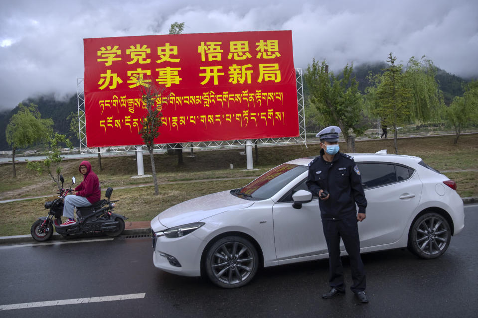 """A police officer directs traffic near a billboard that reads in Chinese """"Study Communist Party history, understand its theories, do practical work, and make new advances"""" in Nyingchi in western China's Tibet Autonomous Region, as seen during a rare government-led tour of the region for foreign journalists, Friday, June 4, 2021. Long defined by its Buddhist culture, Tibet is facing a push for assimilation and political orthodoxy under China's ruling Communist Party. (AP Photo/Mark Schiefelbein)"""