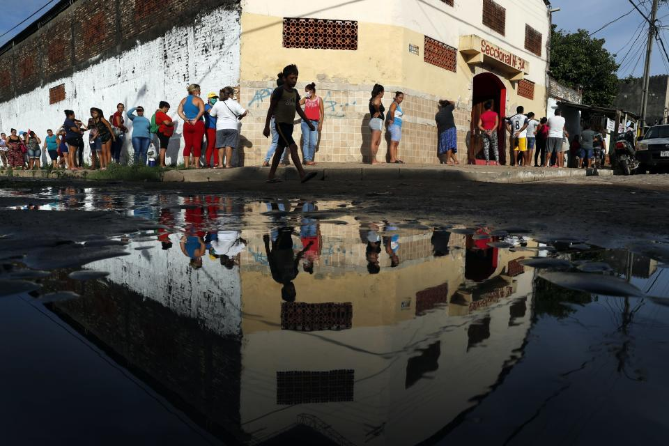 Neighbors line up for free food staples outside Santa Ana primary school in Asuncion, Paraguay, Tuesday, March 31, 2020, part of an already existing food program through the Education Ministry, as people stay home from work amid the spread of the new coronavirus. COVID-19 causes mild or moderate symptoms for most people, but for some, especially older adults and people with existing health problems, it can cause more severe illness or death. (AP Photo/Jorge Saenz)