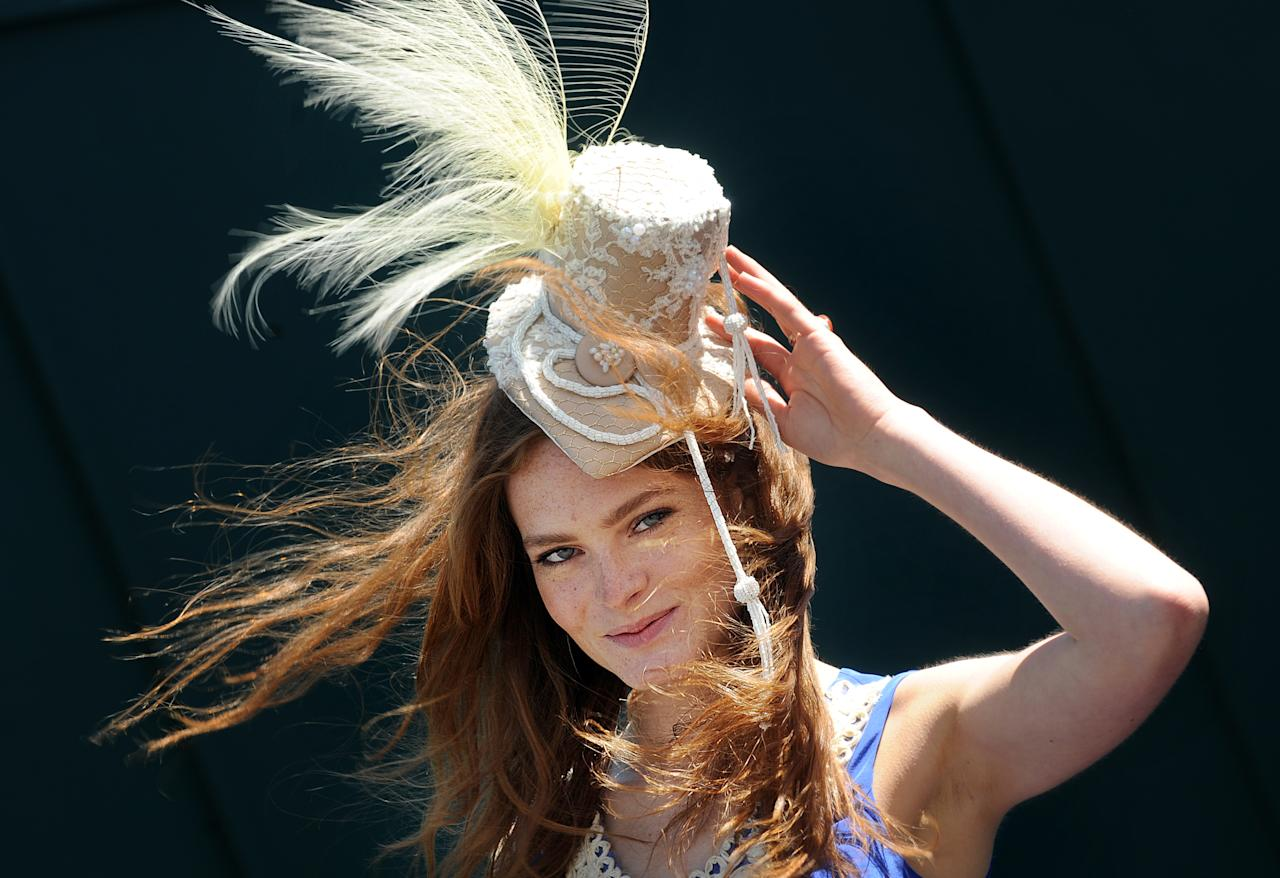 A racegoer poses for photographers on 'Ladies Day' on the first day of the Epsom Derby Festival in Surrey, southern England, on June 3, 2011. The Epsom Derby race will be run Saturday June 4, 2011.  AFP PHOTO / BEN STANSALL (Photo credit should read BEN STANSALL/AFP/Getty Images)