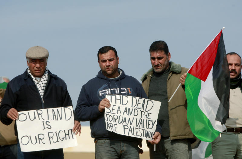 Palestinians hold placards and a national flag near Israeli border police during a demonstration over a proposed Israeli bill seeking to annex the Jordan valley, near the West Bank town of Jericho, Wednesday, Jan. 1, 2014. Israeli hard-liners, including members of Israeli Prime Minister Benjamin Netanyahu's Likud Party, have said the West Bank's Jordan Valley, a strategic area along the border with Jordan, must be annexed by Israel. The Palestinians said they couldn't establish a viable state without the valley, which makes up one-fifth of the West Bank. (AP Photo/Majdi Mohammed)