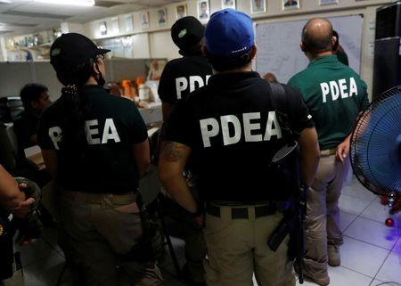 Agents of the Philippine Drugs Enforcement Agency (PDEA) take part in a briefing before a drug raid in Quezon city, Metro Manila