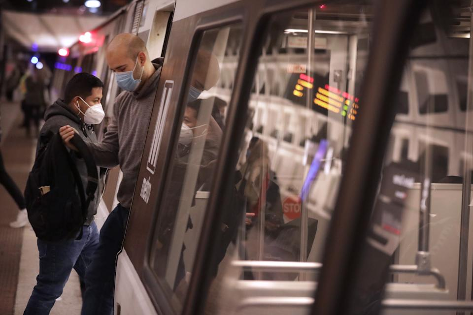 WASHINGTON, DC - DECEMBER 02:  Wearing masks to reduce the risk posed by the coronavirus pandemic, commuters step in and out of a Metro train car at the Metro Center station December 02, 2020 in Washington, DC. Due in part to the drastic decline in ridership because of the ongoing COVID-19 pandemic, Metro is proposing to cut weekend rail service, close 19 of 91 stations, shorten hours of operation, slash bus routes by more than half and lay off 2,400 workers starting in July to meet a $494.5 million deficit in the fiscal year. (Photo by Chip Somodevilla/Getty Images)