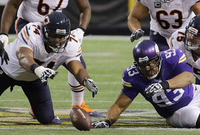 Chicago Bears tackle Jermon Bushrod, left, and Minnesota Vikings defensive tackle Kevin Williams, right, eye a fumble during the fourth quarter of an NFL football game on Sunday, Dec. 1, 2013, in Minneapolis. The Vikings won 23-20 in overtime. (AP Photo/Ann Heisenfelt)