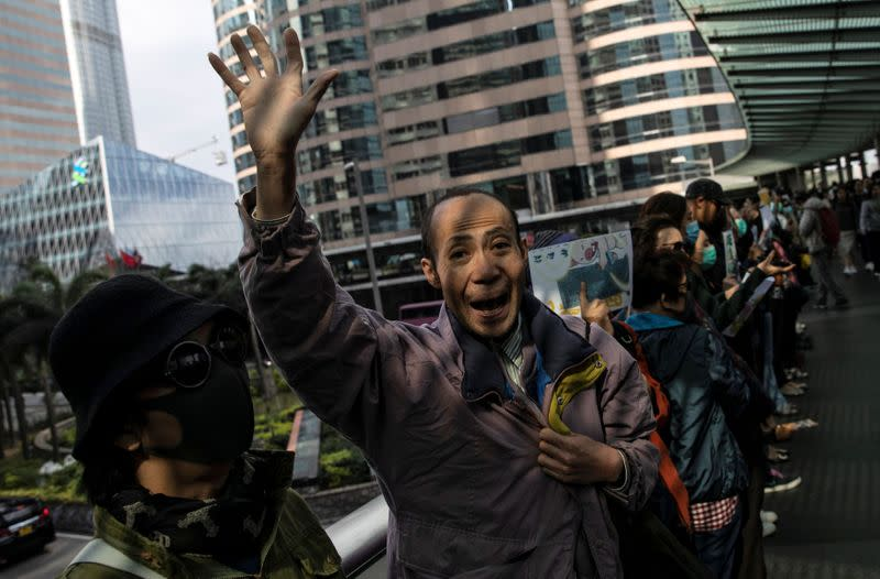 A man shouts slogans as office workers attend a lunch time protest on a pedestrain bridge in Hong Kong