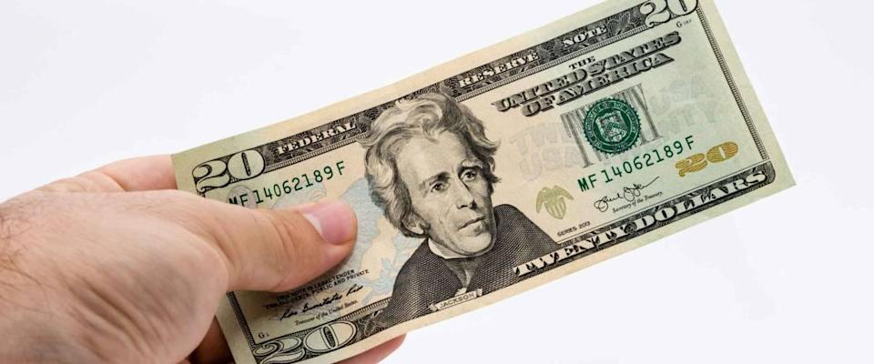 A Caucasian male hand holding a 20 dollar note. This image has a white background.