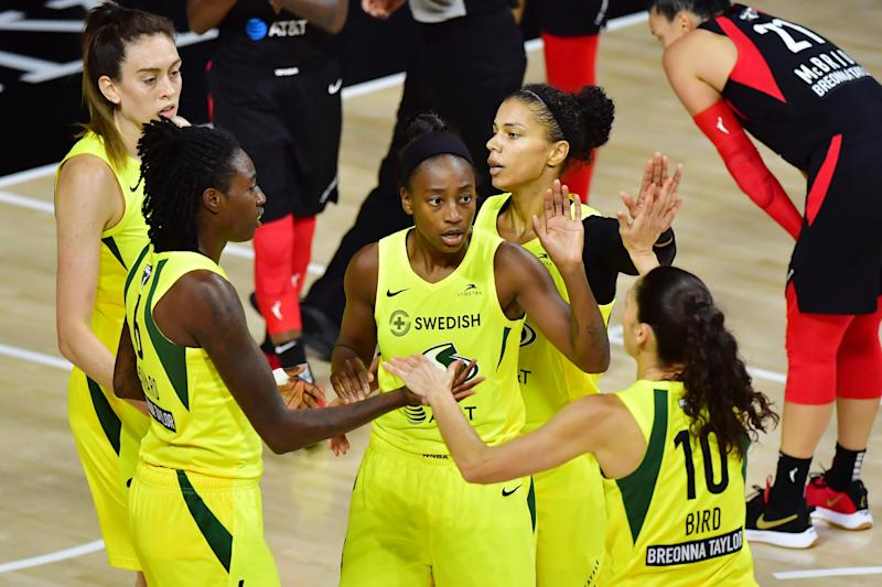 Breanna Stewart, Jewell Loyd, Alysha Clark and Sue Bird stand together on the court with the Aces in the background.