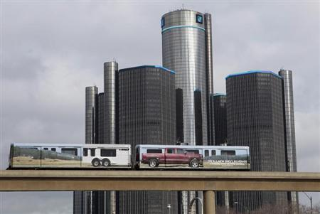 Two cars of the public rail are seen covered with a advertisement for 2014 Chevy Silverado pickup truck as they move past General Motors World Headquarters in Detroit