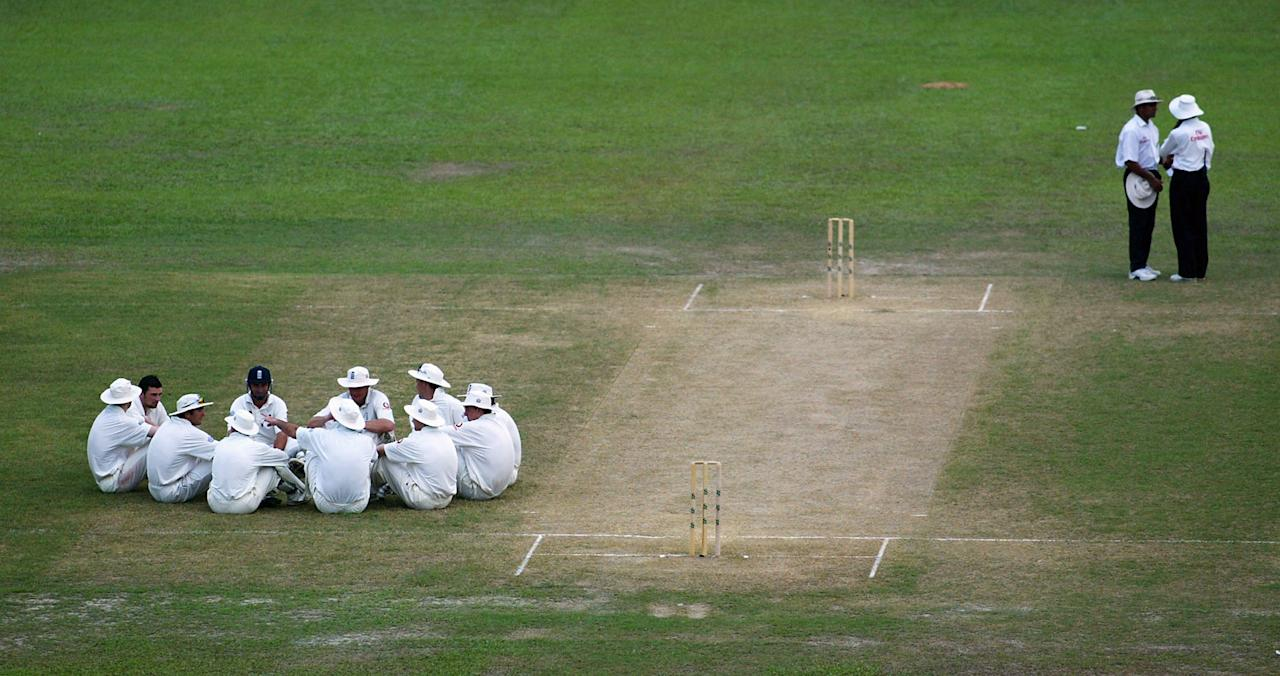 DHAKA, BANGLADESH - OCTOBER 23:  The England team sit waiting for a decision on the bad light as the umpires Aleem Dar and Asoka de Silva discuss during the third day of the First Test match between Bangladesh and England   at the Bangabandhu Stadium October 23, 2003 in Dhaka, Bangladesh. (Photo by Michael Steele/Getty Images)
